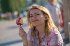 Jolie consommation de jeune femme et pomme de caramel rouge ac?r?e en parc pendant le jour ensoleill? photos libres de droits