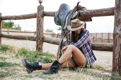Jolie cow-girl se reposant tout en se penchant sur la barrière de ranch Photo stock