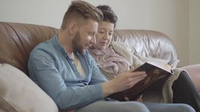 Jolie dame âgée de portrait et petit-fils adulte reposant à la maison de vieilles photos de observation dans le grand album photo banque de vidéos