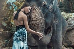 Jolie dame étreignant un bel éléphant d'Asie Image libre de droits