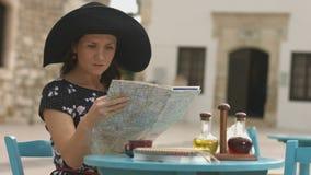 Jolie dame étudiant la carte de ville, recherchant le logement, hôtel, restaurant, café banque de vidéos