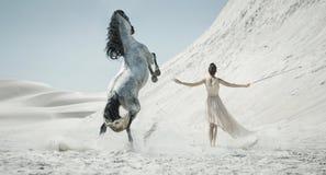 Jolie dame avec le cheval énorme sur le désert Photographie stock