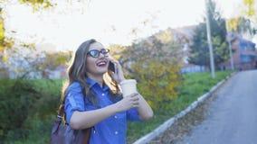 Jolie dame d'affaires parlant du téléphone, du café potable et souriant au parc 4K banque de vidéos