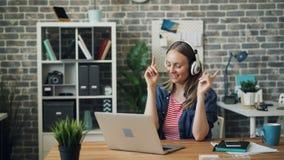 Jolie dame dans des écouteurs écoutant la musique dans la danse de bureau soulevant des bras banque de vidéos