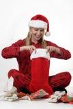 Jolie dame dans le chapeau de Santa regardant à l'intérieur de son bas Images libres de droits