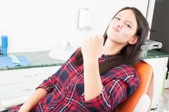 Jolie dame montrant le poing dans la chaise de dentiste Image stock
