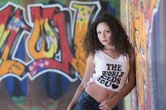 Jolie dame se penchant sur un mur de graffiti Image stock