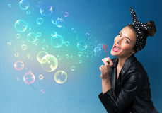 Jolie dame soufflant les bulles colorées sur le fond bleu Images stock