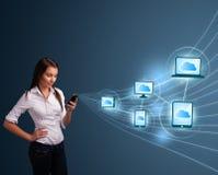 Jolie dame tapant sur le smartphone avec le calcul de nuage Photo stock