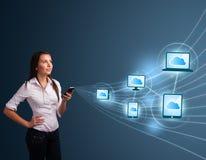 Jolie dame tapant sur le smartphone avec le calcul de nuage Photographie stock libre de droits
