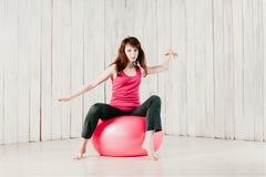 Jolie danse de fille sur un fitball rose, tache floue de mouvement, clé élevée photographie stock