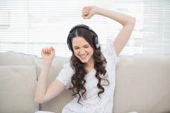 Jolie danse de jeune femme tout en écoutant la musique Image stock