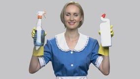 Jolie domestique de maison tenant deux bouteilles détersives banque de vidéos