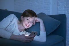 Jolie et heureuse femme rouge de cheveux sur son 20s ou 30s se trouvant sur le divan à la maison ou lit utilisant le téléphone po Image stock