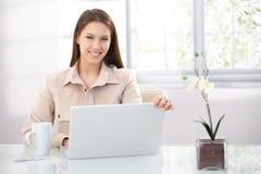 Jolie femelle à l'aide de l'ordinateur portatif à la maison souriant Image stock
