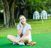 Jolie femme à l'aide de son téléphone dans le parc Images stock