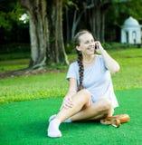 Jolie femme à l'aide de son téléphone dans le parc Photo libre de droits