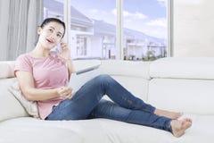 Jolie femme à l'aide du comprimé à la maison Photographie stock libre de droits