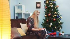 Jolie femme écrivant un postcad près de l'arbre de Noël banque de vidéos