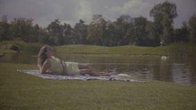Jolie femme élégante se reposant en parc d'été clips vidéos