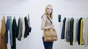 Jolie femme adulte prenant au sac d'une femme de quelqu'un la main et posant avec elle dans un vestiaire banque de vidéos