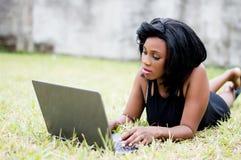 Jolie femme africaine s'étendant sur l'herbe et lisant de son ordinateur portable photo stock