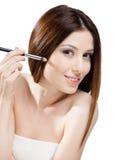 Jolie femme appliquant le maquillage avec la brosse Photographie stock libre de droits