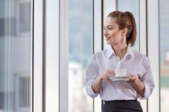 Jolie femme appréciant la pause-café sur son lieu de travail photo stock