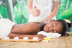 Jolie femme appréciant un massage de fines herbes de compresse Images stock