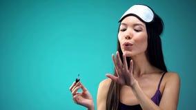 Jolie femme asiatique soufflant sur le vernis à ongles, les pyjamas de port et le bandeau, soin photographie stock