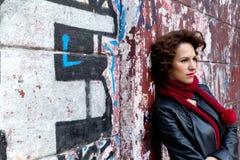 Jolie femme attendant au mur de graffiti Photos stock