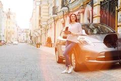 Jolie femme attendant tandis que son remplissage de voiture Photographie stock libre de droits