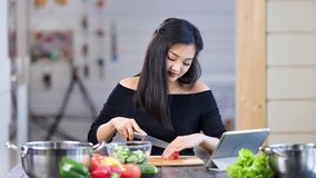 Jolie femme au foyer féminine asiatique moderne faisant cuire la salade fraîche coupant le légume utilisant le couteau clips vidéos