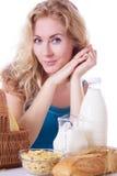 Jolie femme avec du lait et des cornflakes à la table photo libre de droits