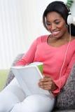 Jolie femme avec la musique de écoute d'écouteurs Photos stock