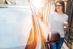 Jolie femme avec la tasse de café touchant sa voiture Images stock
