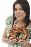 Jolie femme avec le dirndl et le bretzel Photographie stock