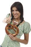 Jolie femme avec le dirndl et le bretzel Image stock
