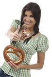 Jolie femme avec le dirndl et le bretzel Images stock