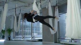 Jolie femme avec le grand corps accrochant avec sa tête vers le bas dans l'hamac de yoga au centre de fitness moderne avec grand  banque de vidéos