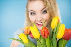 Jolie femme avec le groupe jaune rouge de tulipes Photos stock