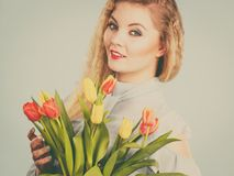 Jolie femme avec le groupe jaune rouge de tulipes Images stock