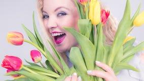 Jolie femme avec le groupe jaune rouge de tulipes Image libre de droits