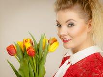 Jolie femme avec le groupe jaune rouge de tulipes Photo libre de droits