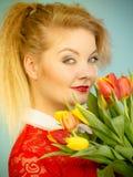 Jolie femme avec le groupe jaune rouge de tulipes image stock