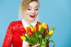 Jolie femme avec le groupe jaune rouge de tulipes photographie stock