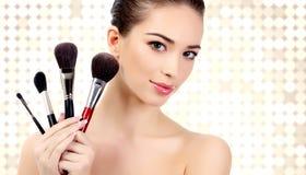 Jolie femme avec les brosses cosmétiques Photos stock