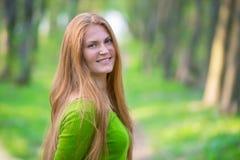 Jolie femme avec les cheveux rouges en parc Photographie stock libre de droits