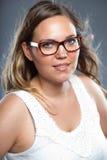 Jolie femme avec les verres de port de longs cheveux bruns Photographie stock
