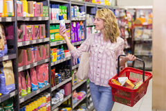 Jolie femme blonde de sourire regardant le produit Photographie stock